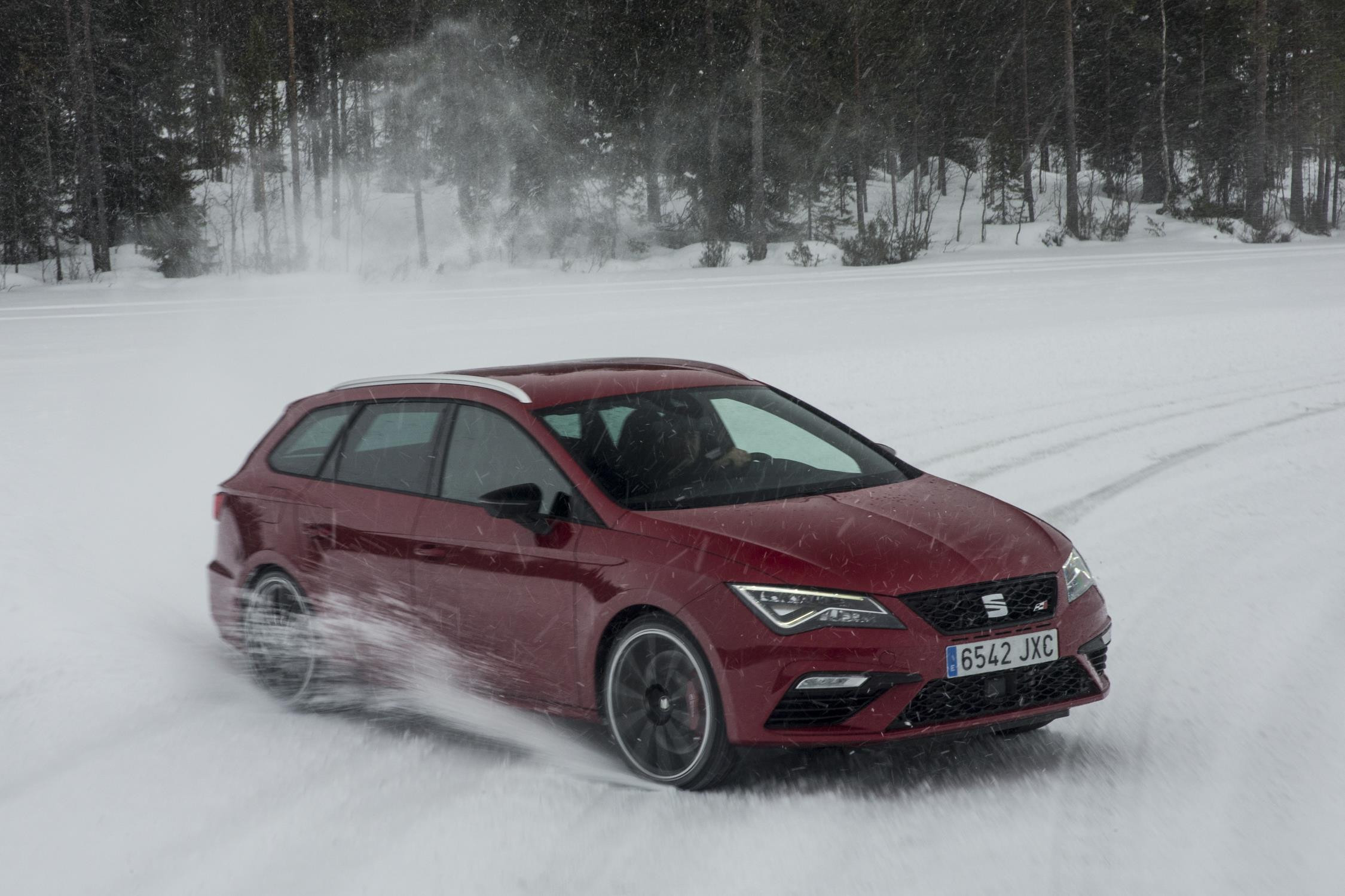Red SEAT Leon ST driving in a forest in thick snow