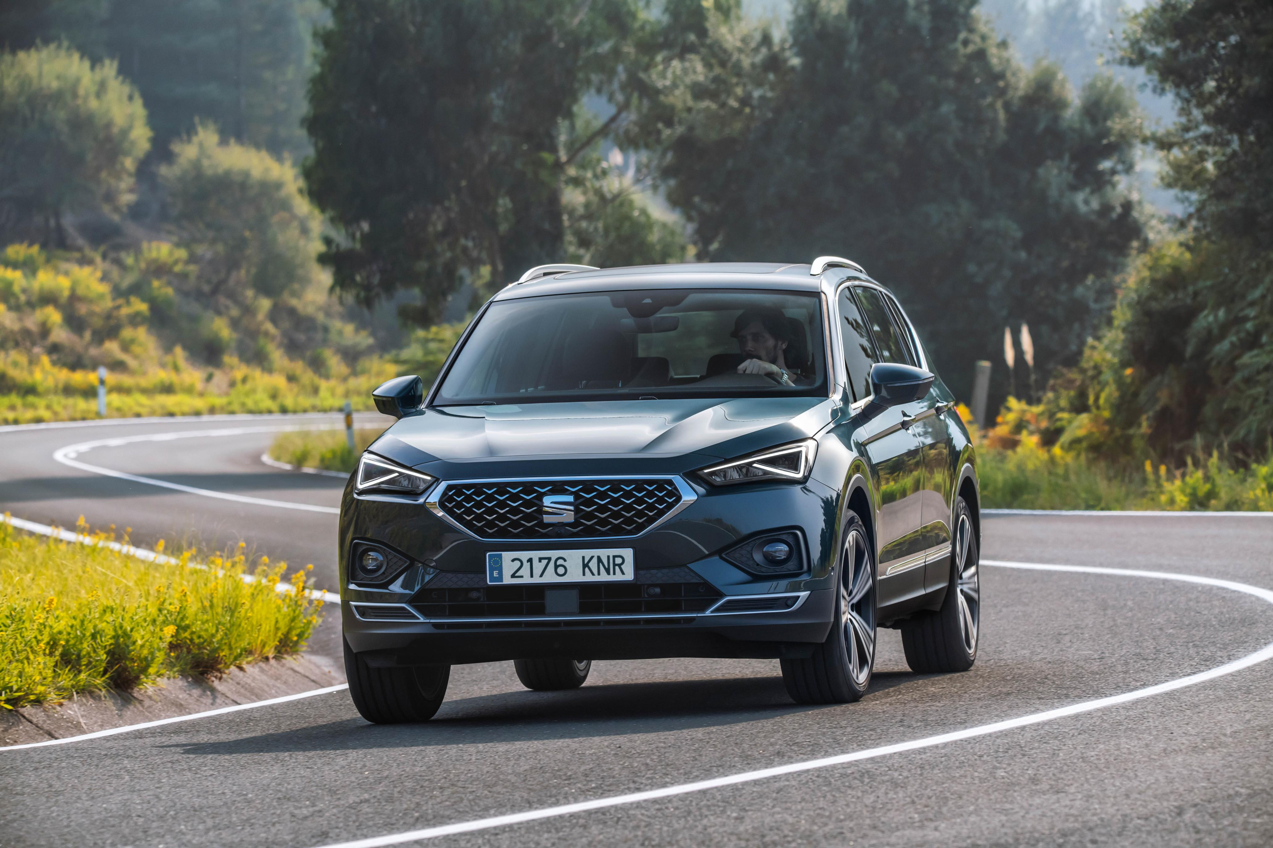 Dark grey SEAT Tarraco driving head on towards you down a winding country lane