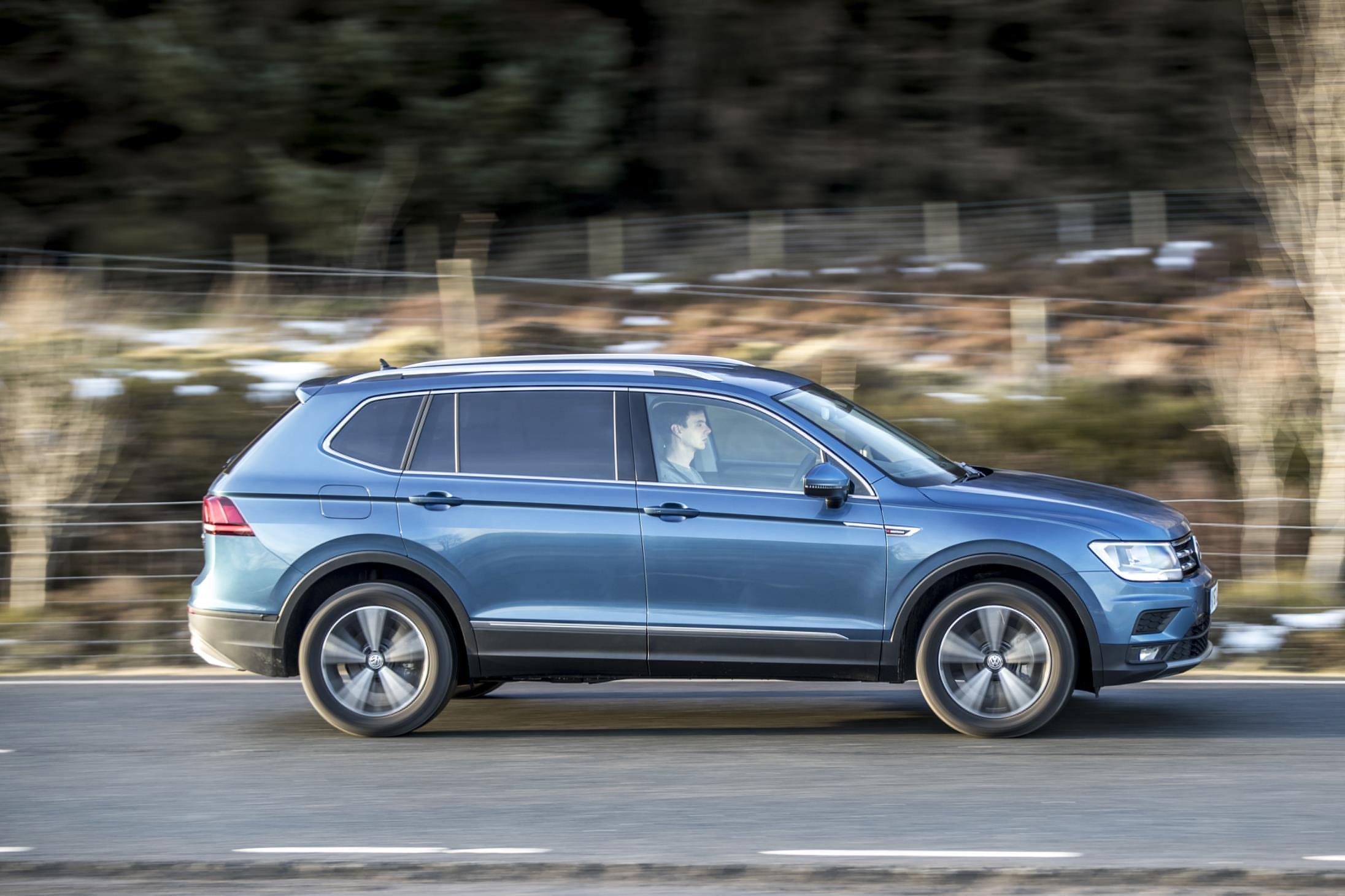 Metallic blue Volkswagen Tiguan Allspace driving past you side-on