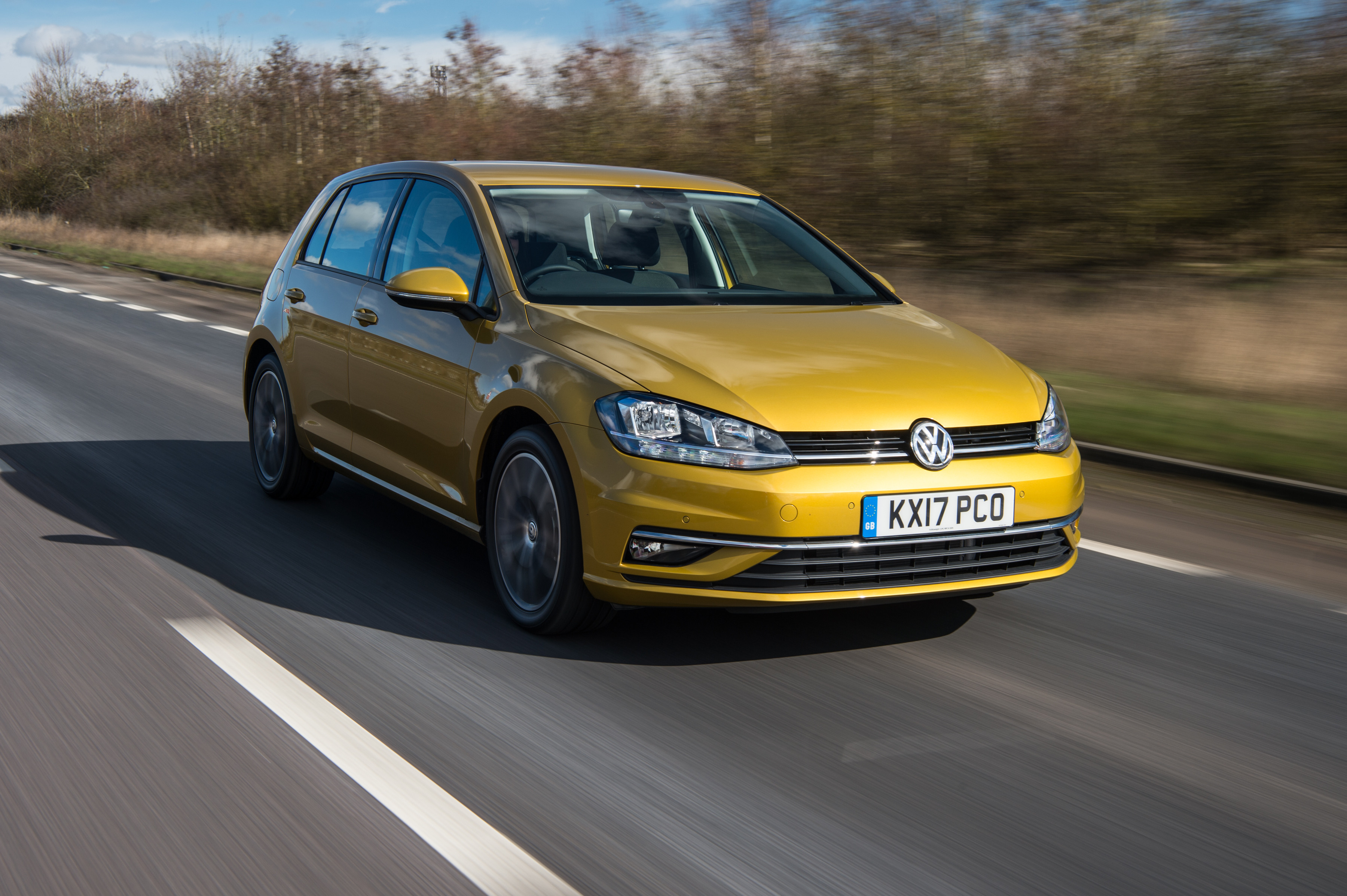 Gold metallic Volkswagen Golf driving towards you down the road