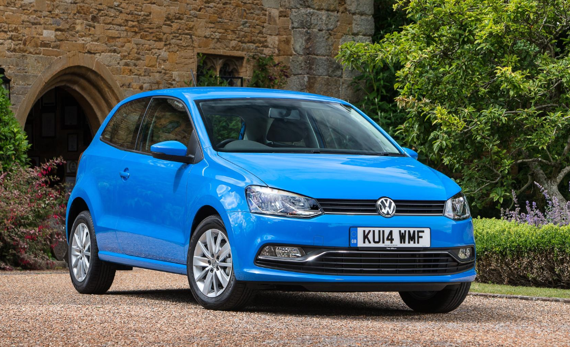 Bright blue Volkswagen Polo parked on gravel outside old gatehouse