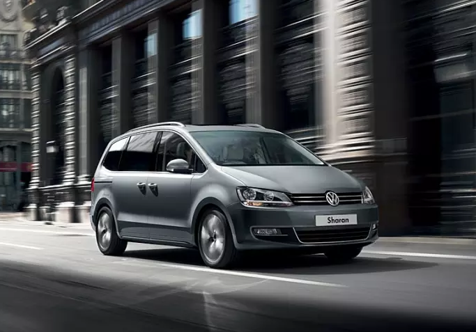 Flat grey Volkswagen Sharan speeding through the city
