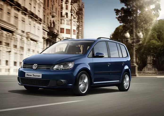 Blue Volkswagen Touran driving down a European city street