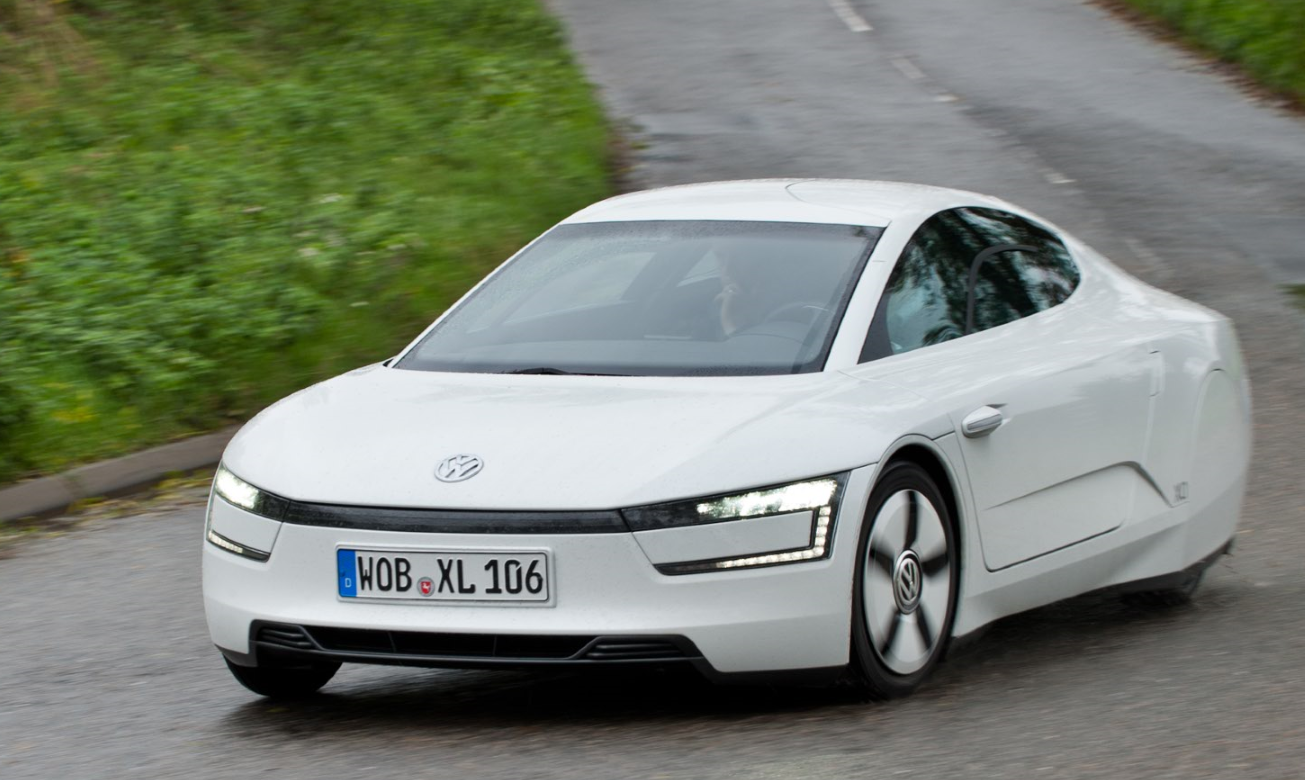 White Volkswagen XL driving on the road round a corner with lots of greenery