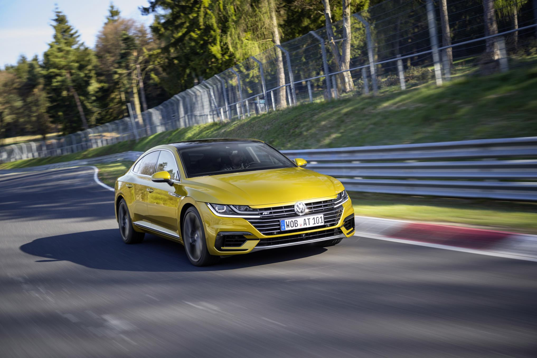 Yellow Volkswagen Arteon driving round a race track