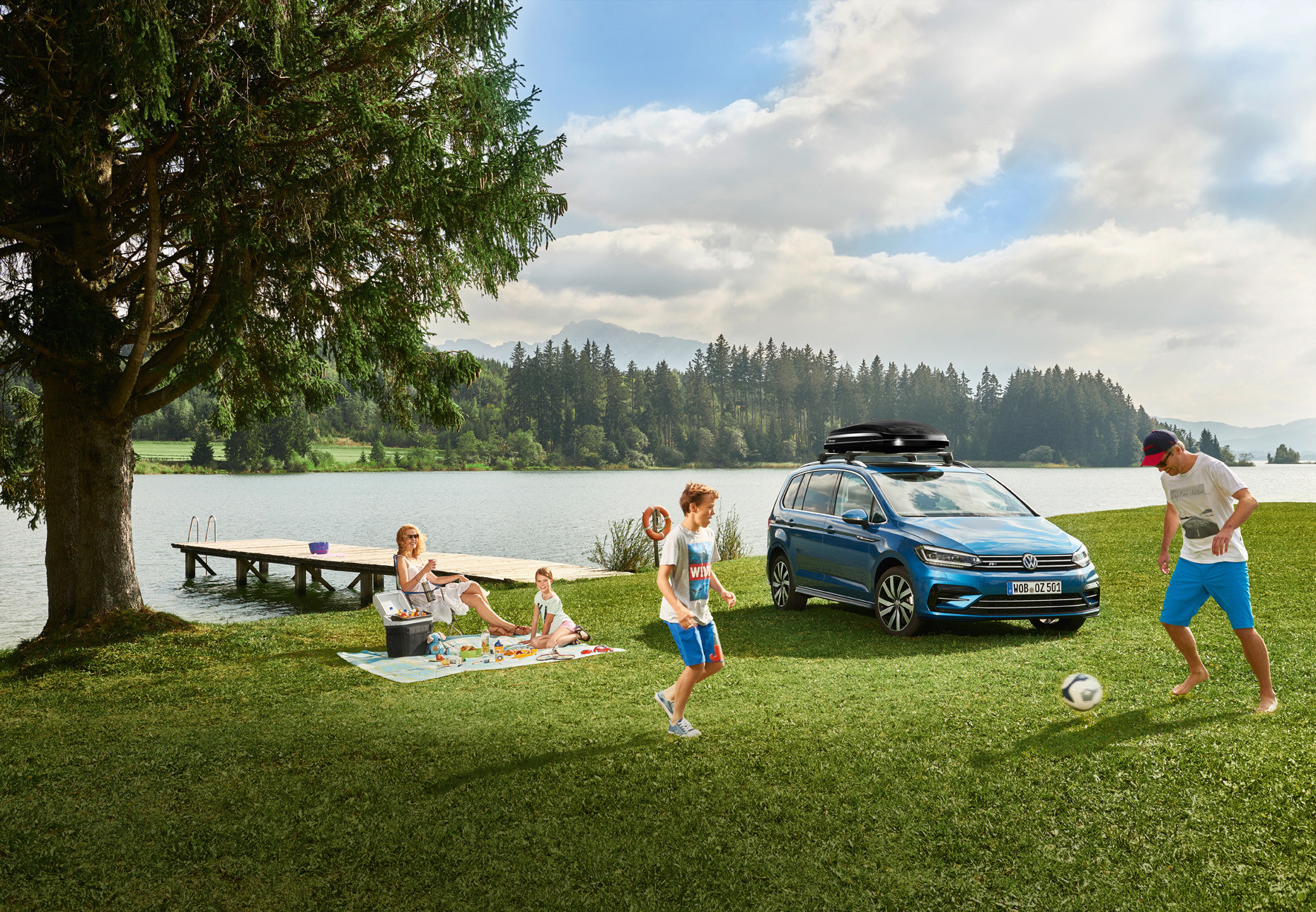 Bright blue Volkswagen Touran parked on grass by a lake with family playing football