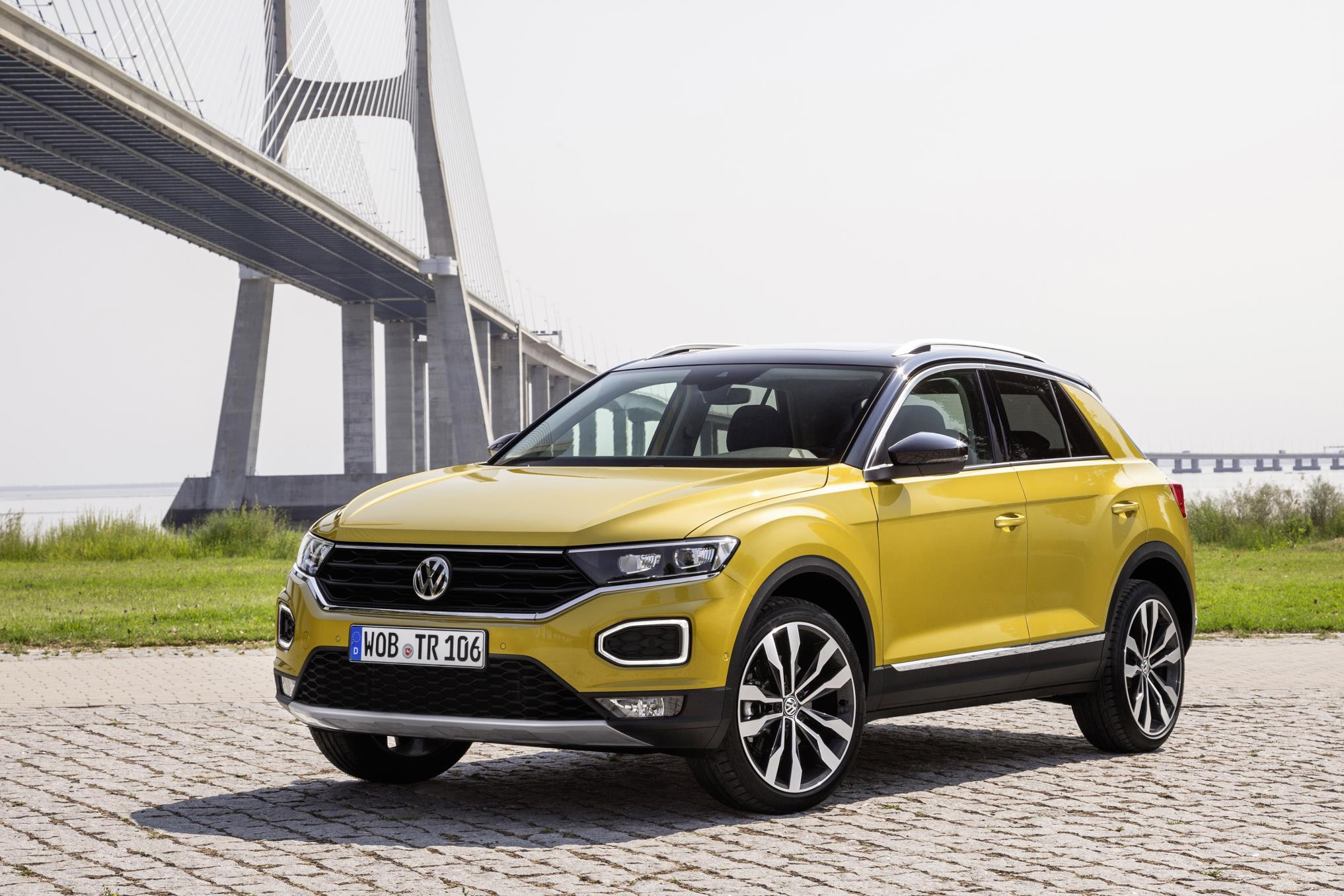 Yellow Volkswagen T-Roc parked by a bridge