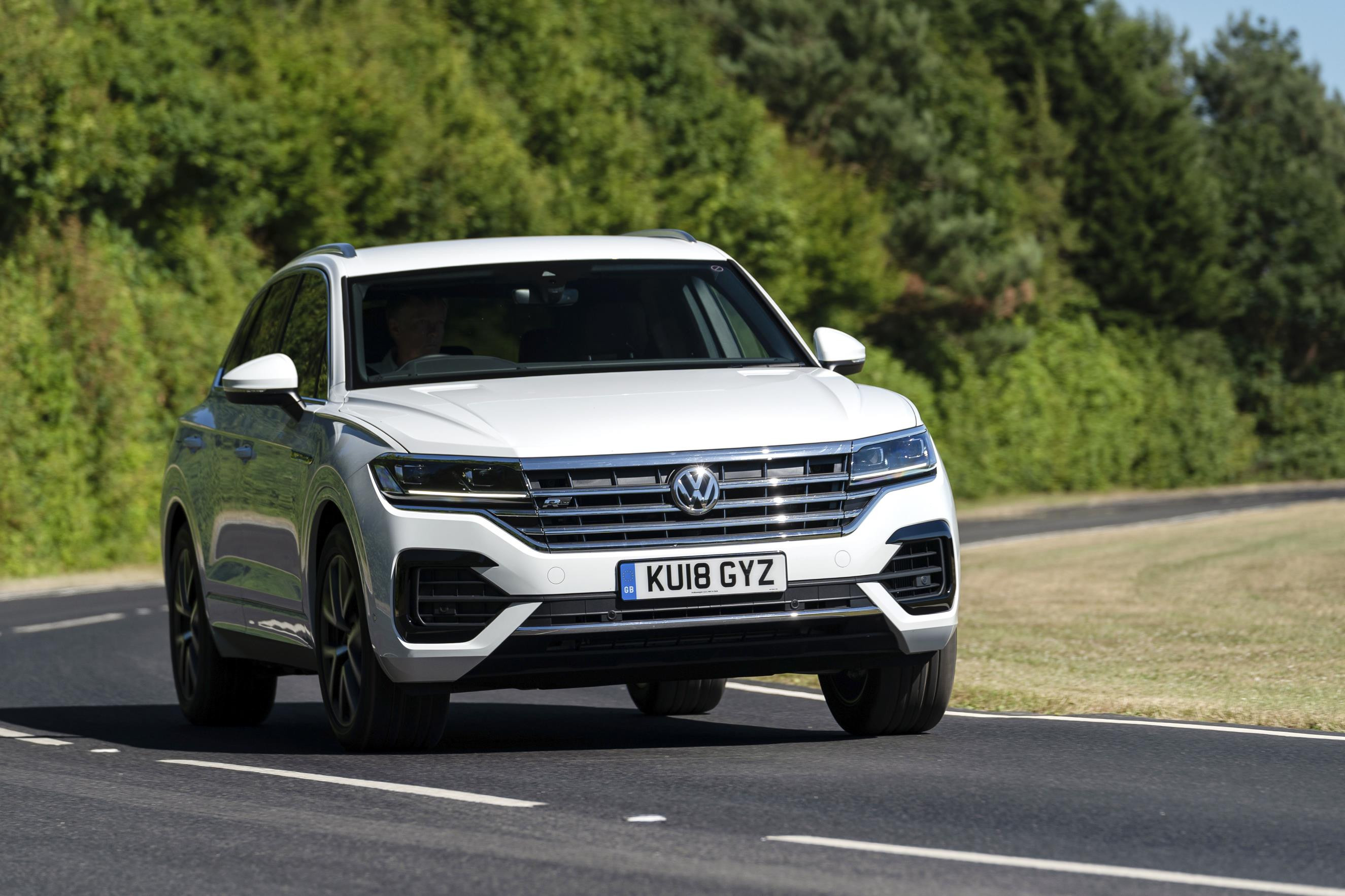 White Volkswagen Touareg driving towards you round a bend