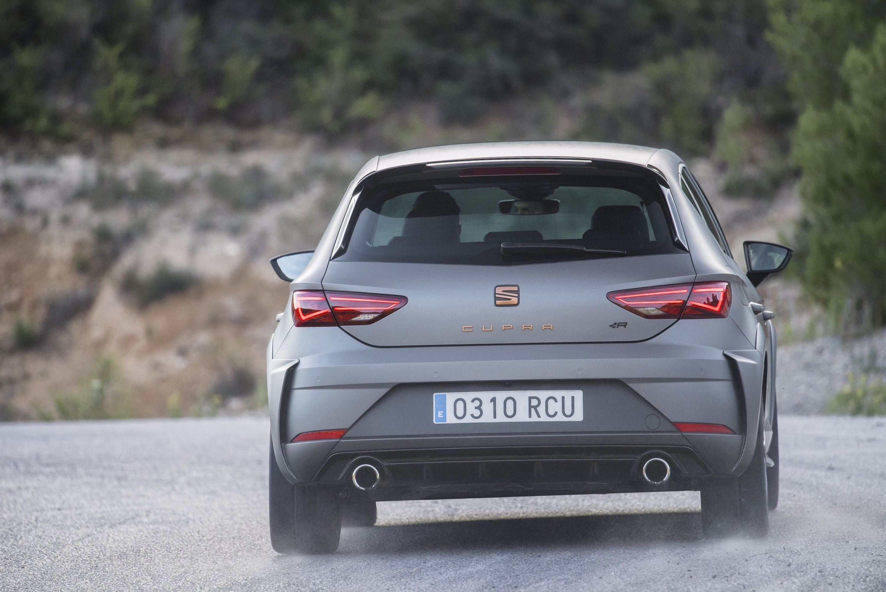 Rear photo of a SEAT Leon Cupra driving away from the camera on a dusty road with the dust rising up