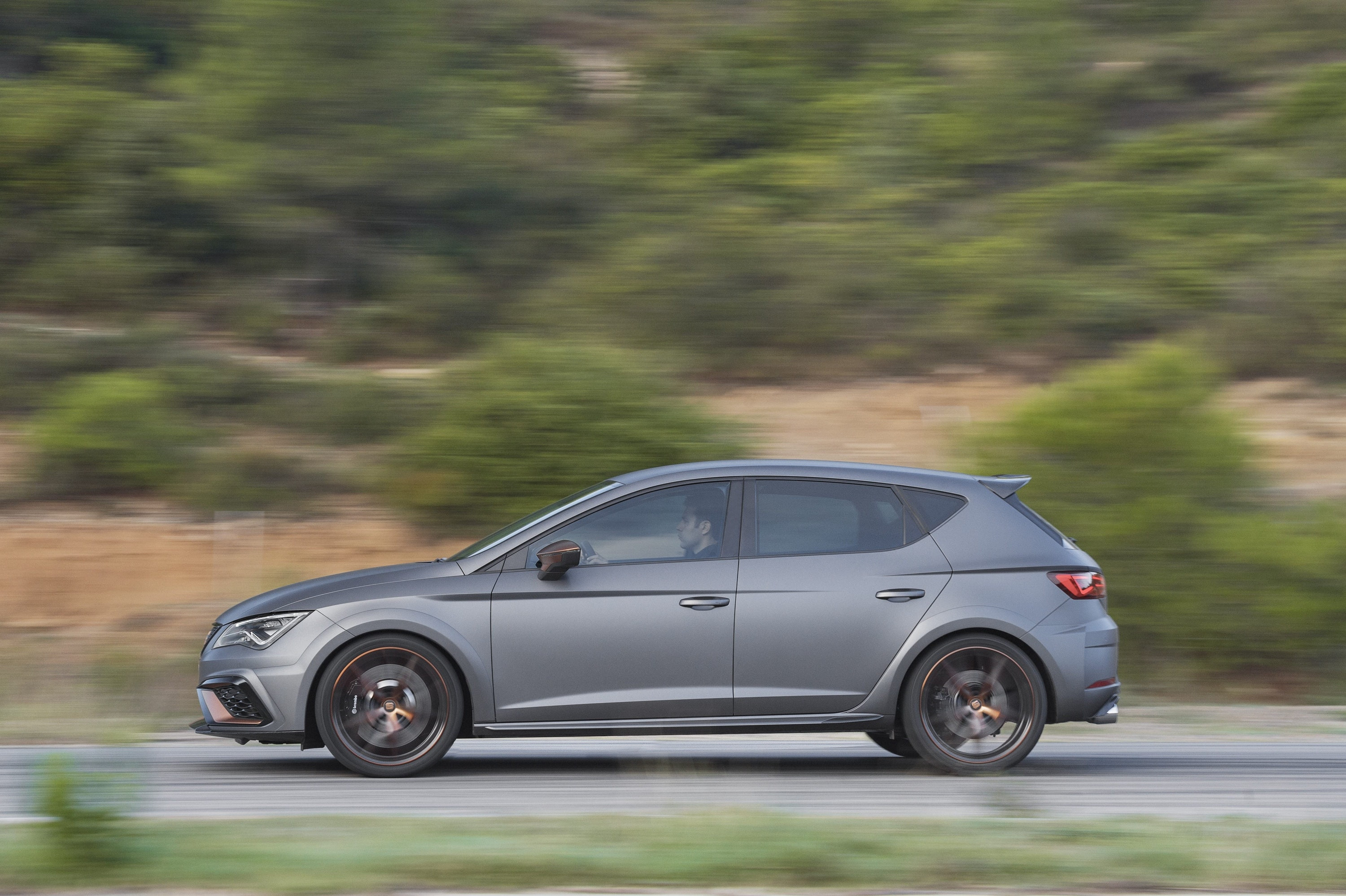 Grey SEAT Leon Cupra from the side driving along a road
