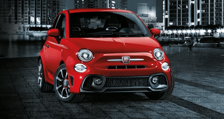 Bright red Abarth 595 with a dark city background behind it