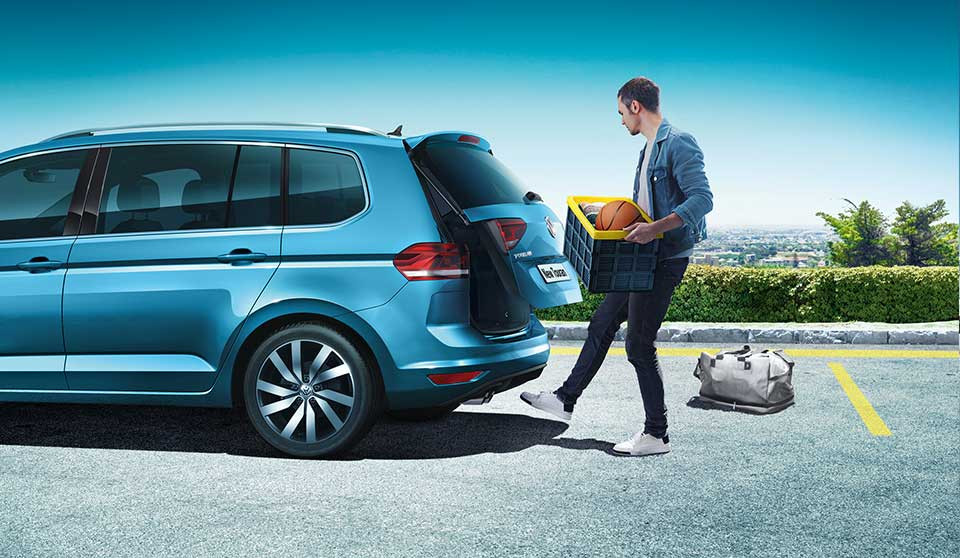Man putting stuff in Volkswagen Touran boot