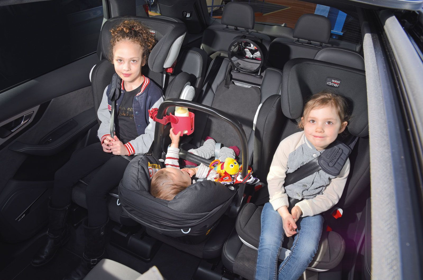 Rear seat with three child seats in it