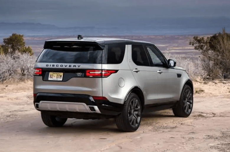 Silver Land Rover Discovery parked on a beach seen from the rear