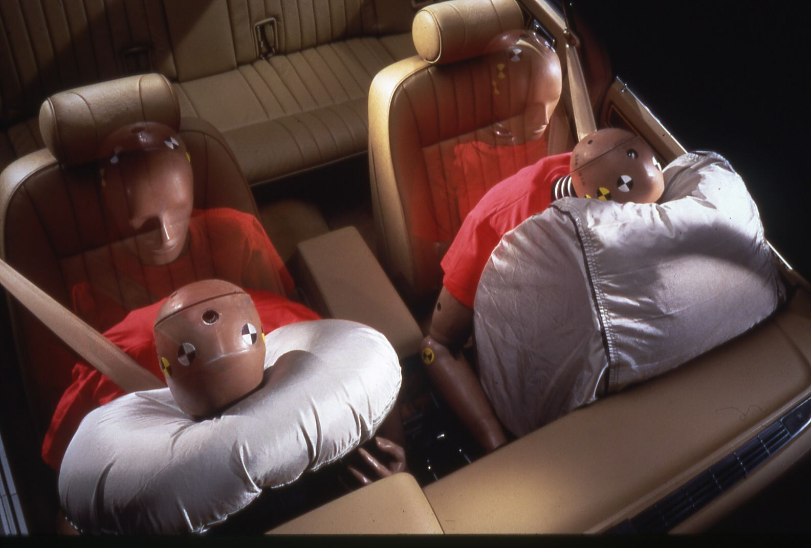 Crash test dummies showing how forceful an airbag going off into a baby seat can be