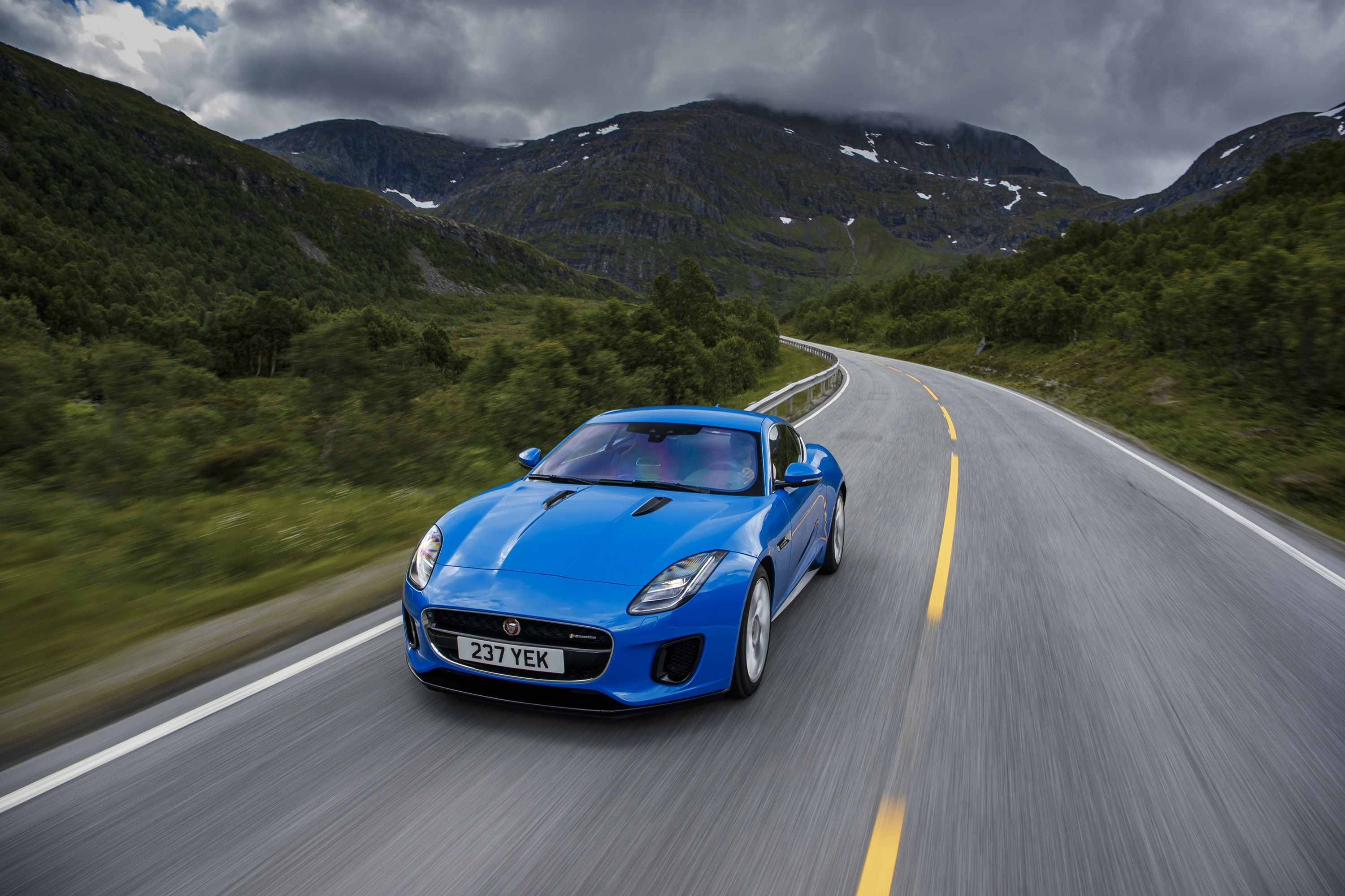 Jaguar F-Type driving down road from front