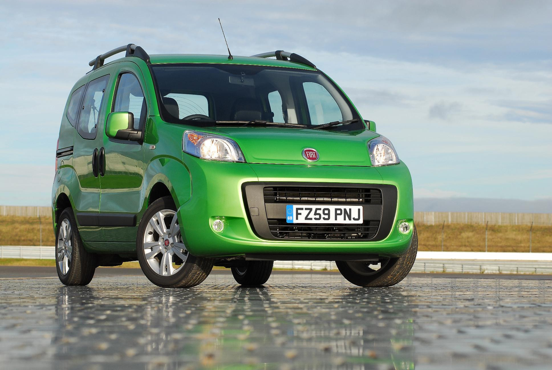Bright green Fiat Qubo parked by a beach
