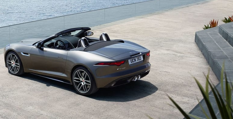 Silver Jaguar F-Type convertible parked looking out to see.