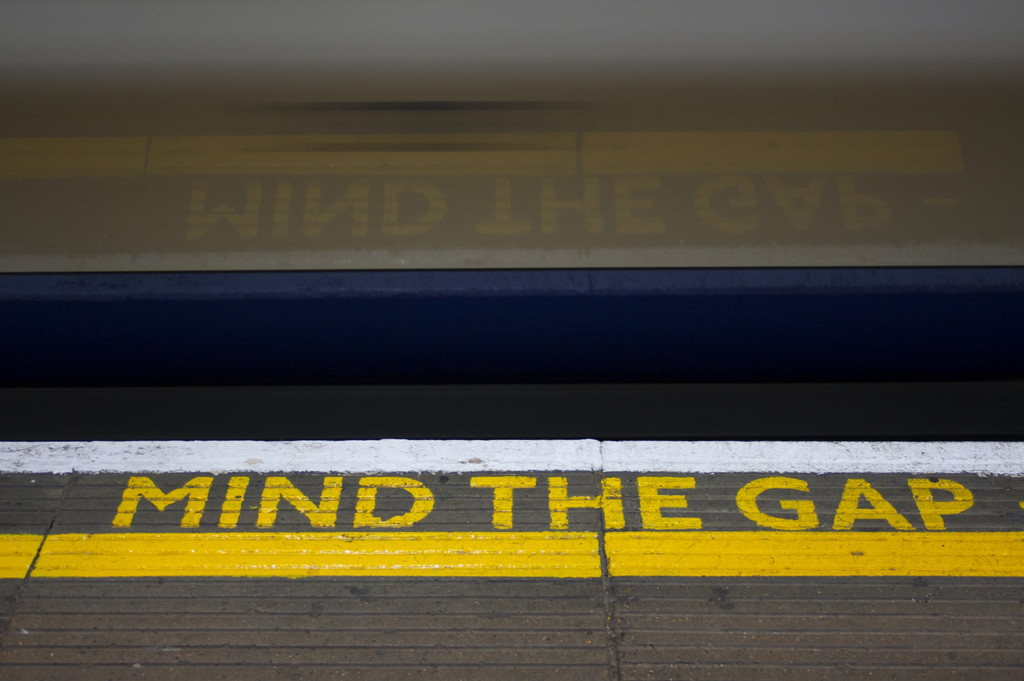 Mind the Gap sign at the edge of a train station platform