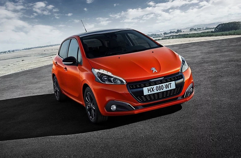 Orange Peugeot 208 parked forwards with a beach backdrop