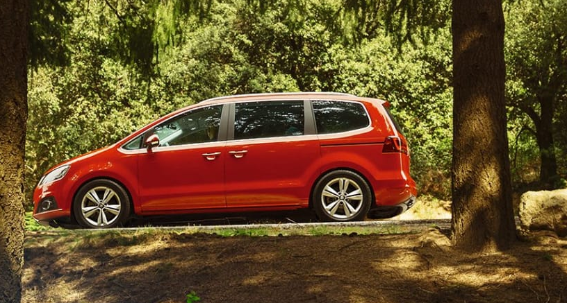 Red SEAT Alhambra in gladed woodland with sunlight dappled through the leaves