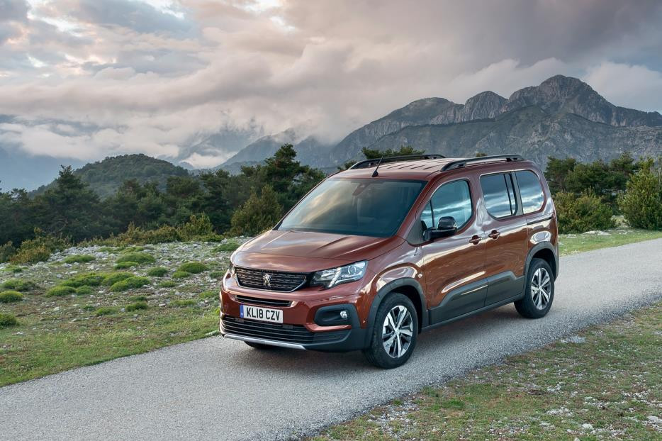 Brown metallic Peugeot Rifter two thirds side on in dramatic countryside